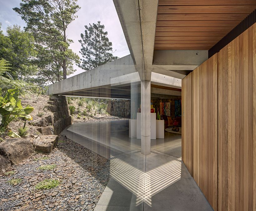 The wood-paneled surfaces add a warm and welcoming touch to the design and to the concrete frame