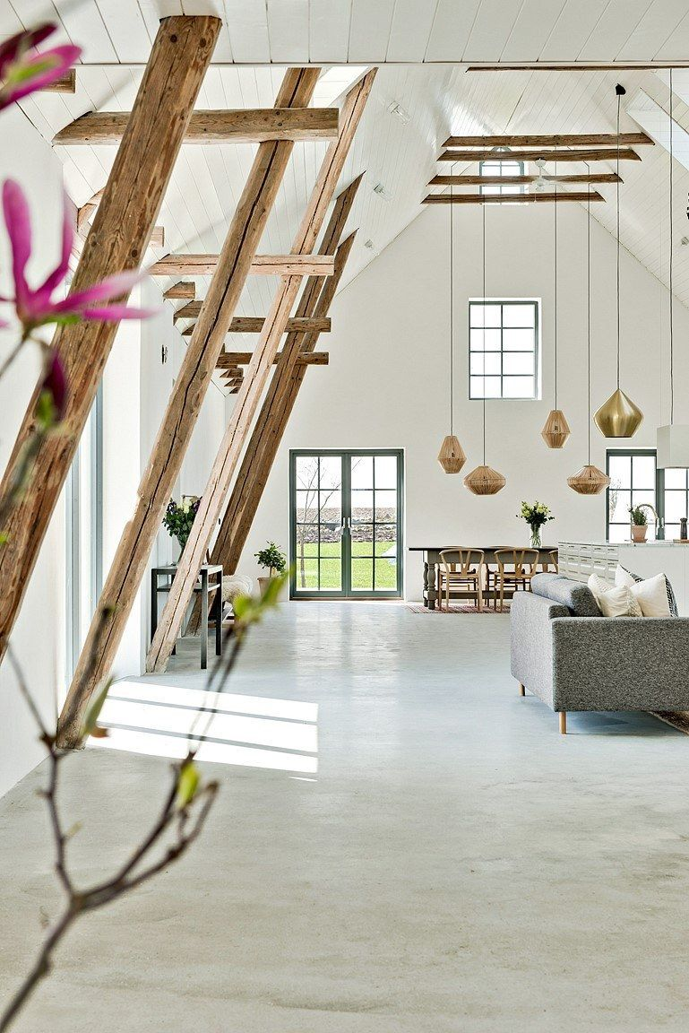 A series of low-hanging pendant lamps are suspended from the high ceiling, complementing the lounge area