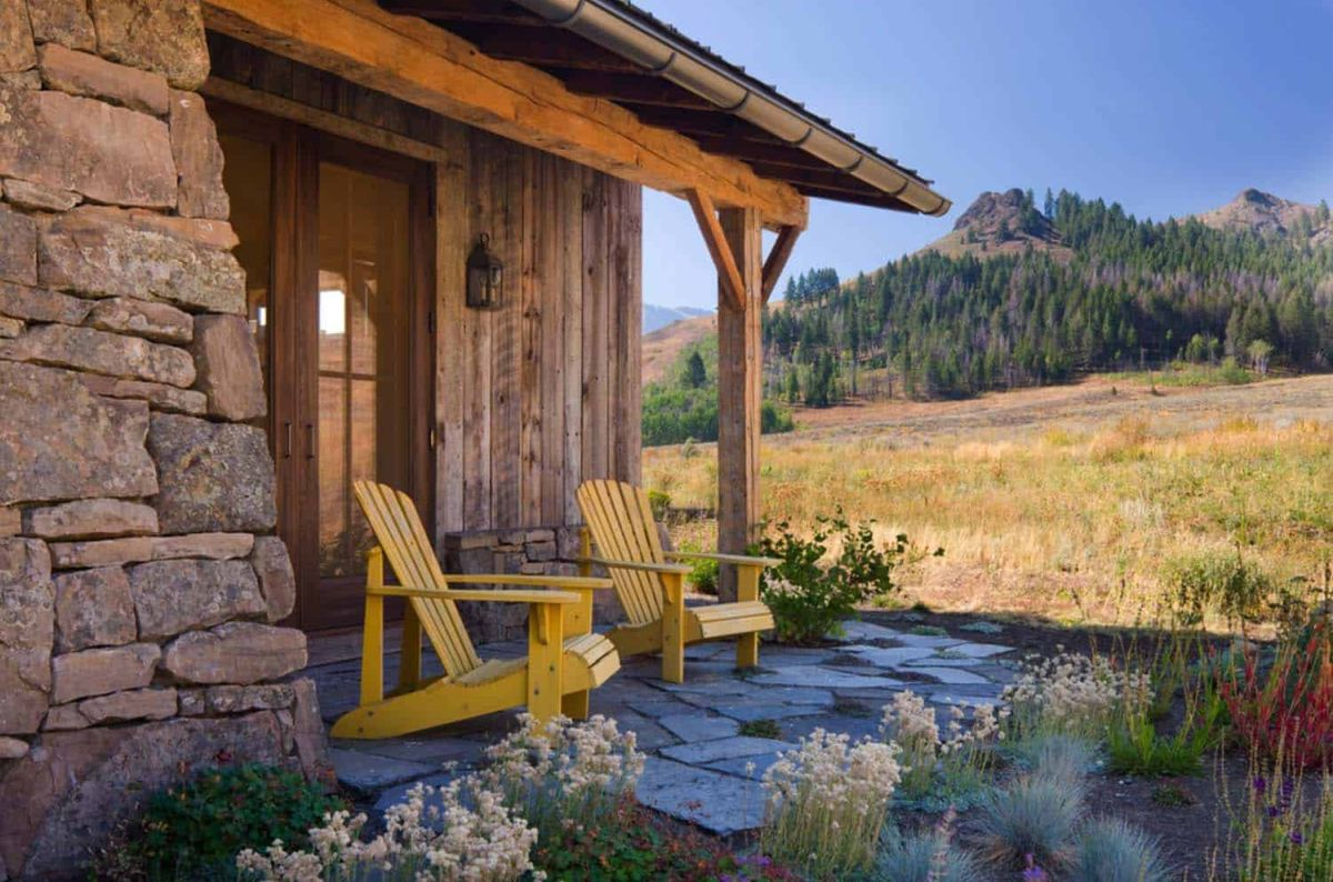 Two classic Adirondack chairs sit just outside the entrance, extending the living areas outside