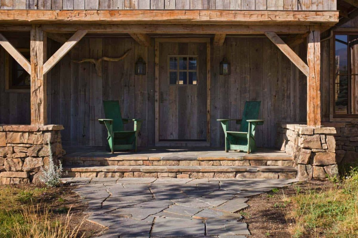 A covered patio built out of wood and stone frames the barn's new extension