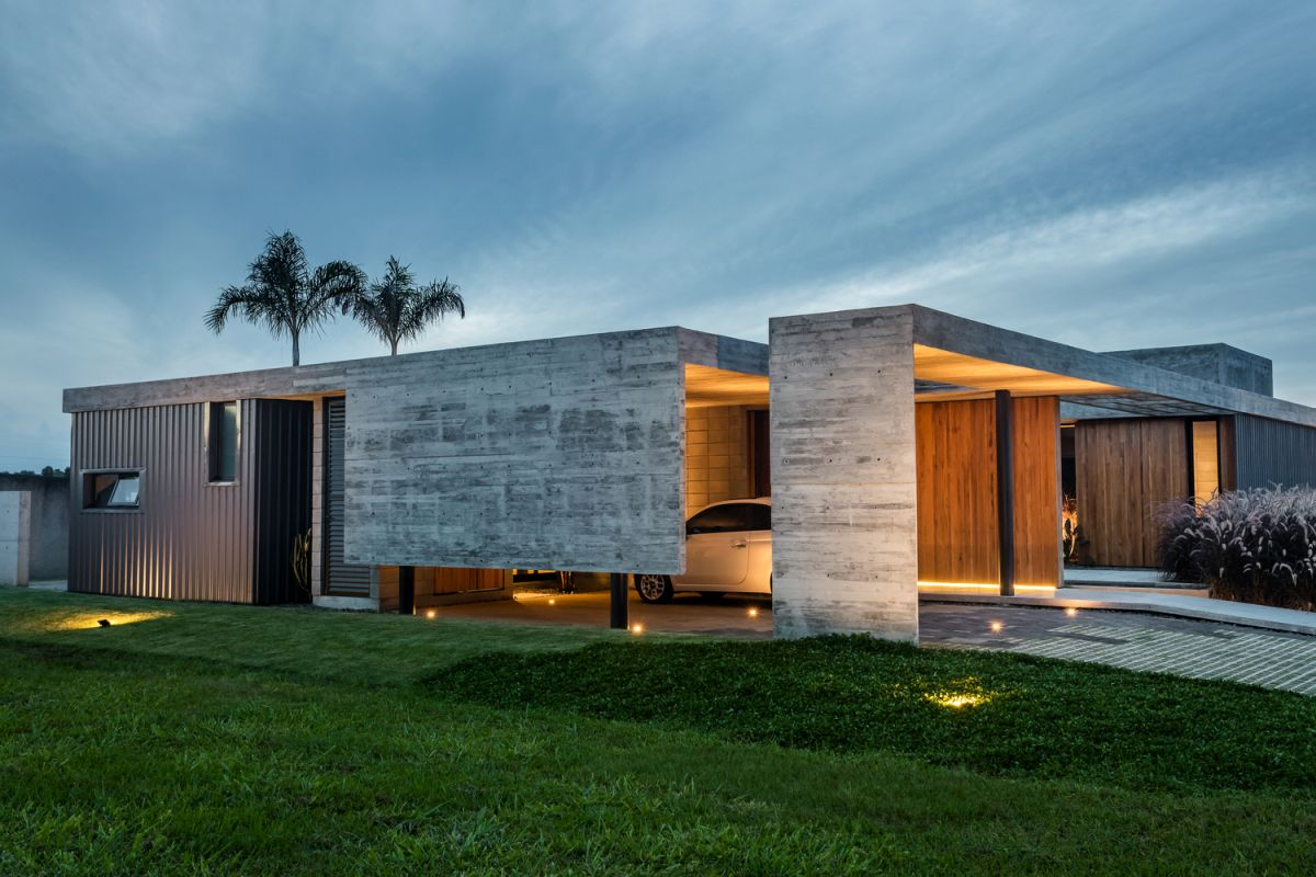 The exterior of the house is a collection of concrete and wooden blocks which are arranged around a courtyard