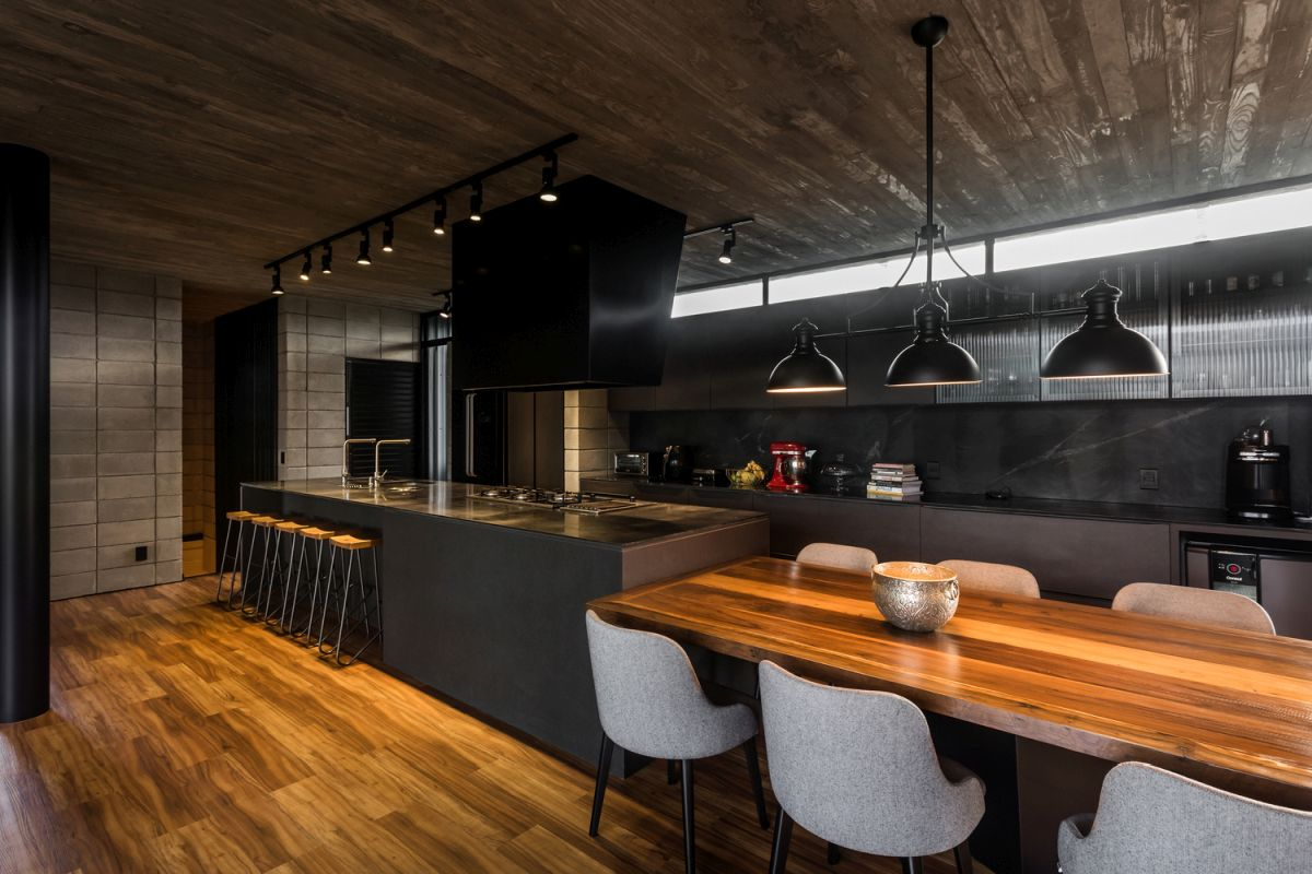 The kitchen and dining area are designed with darker color tones for a warm and cozy vibe