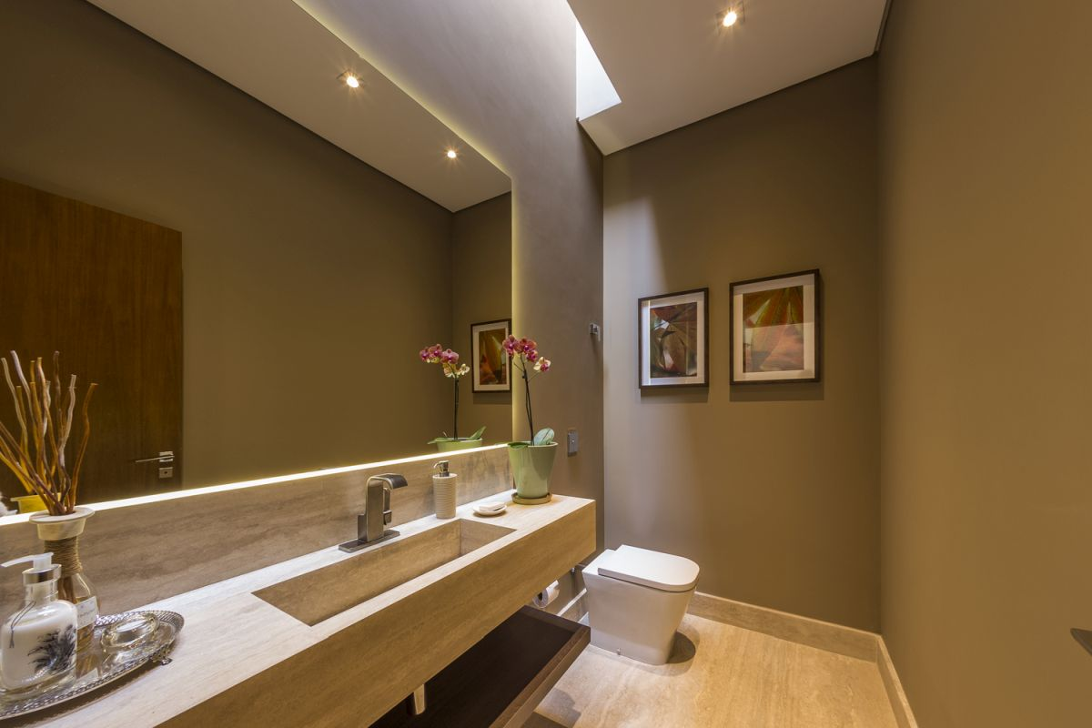 A huge backlit wall mirror enlarges the bathroom visually while also highlighting its beautiful colors