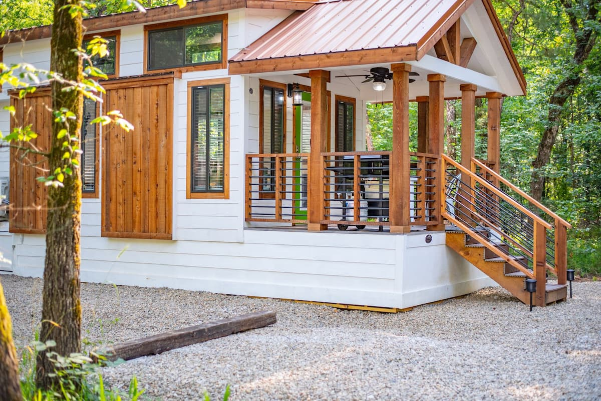 The exterior of the cabin showcases a beautiful combination of natural wood and white paneling
