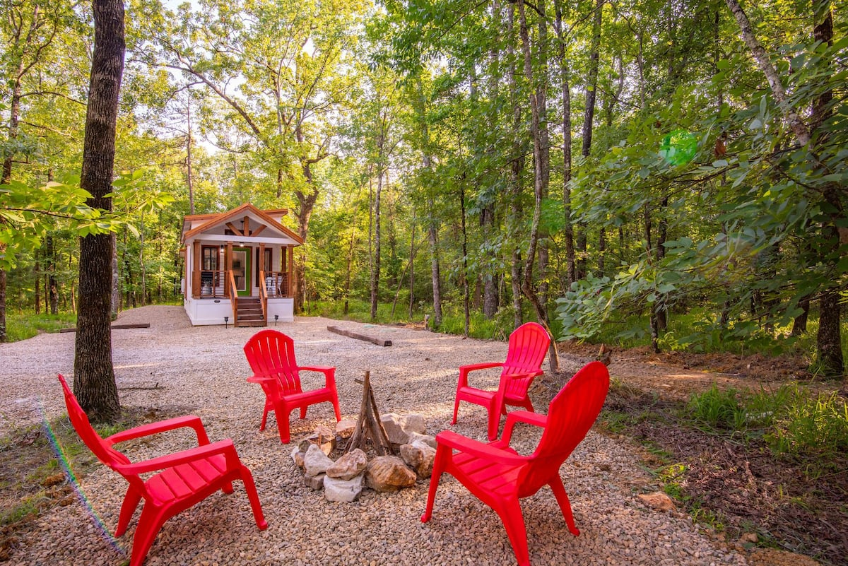 A fire pit area is placed some distance away from the cabin, visible from the front porch