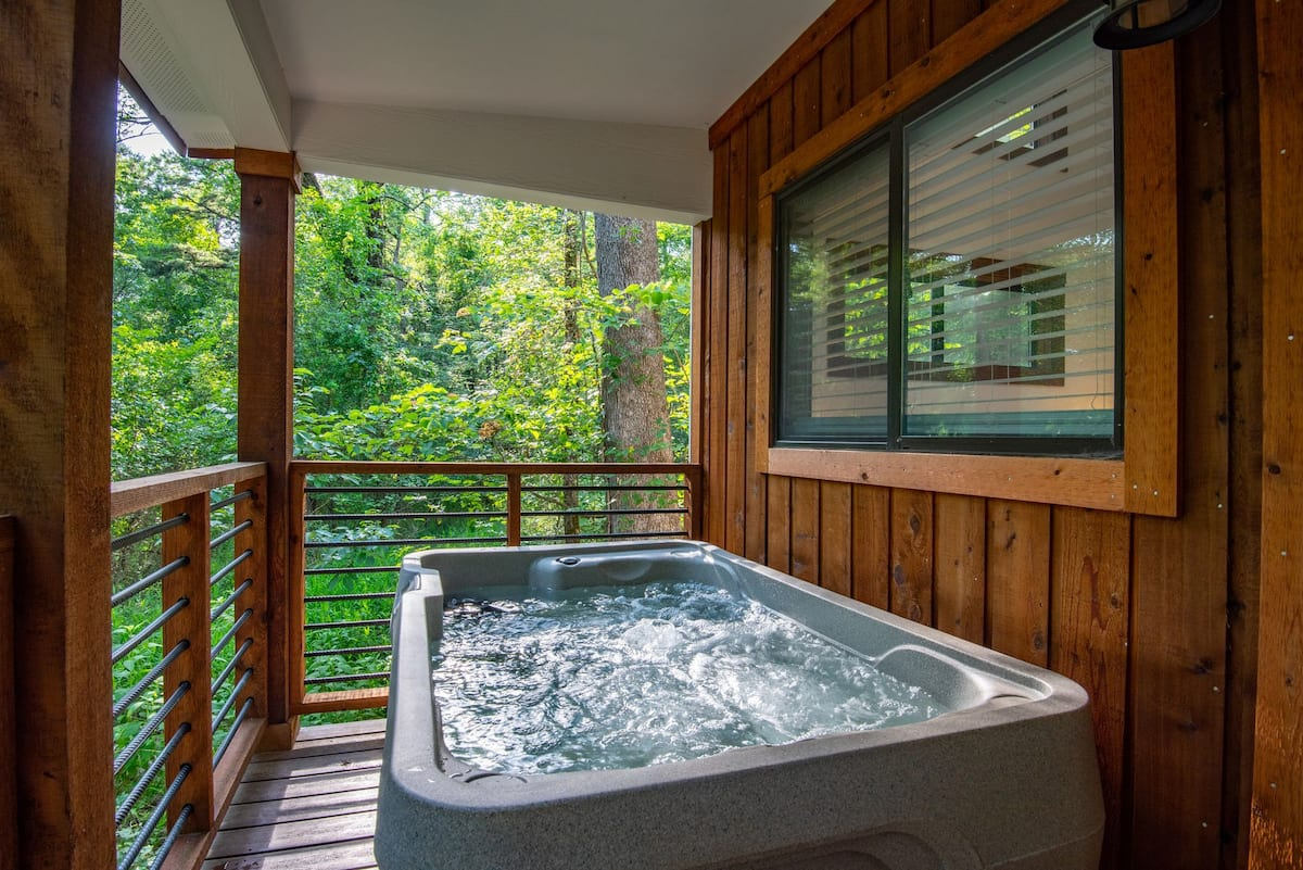 The back porch is where the hot tub can be found on one side and a grill on the other