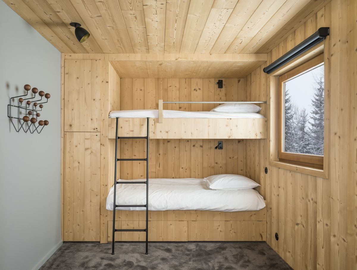 A custom double bunk bed system give this tiny bedroom a super warm and cozy look