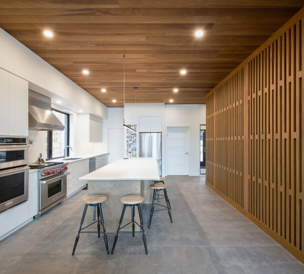The wood ceiling and dividing wall add warmth to the kitchen which has a white design
