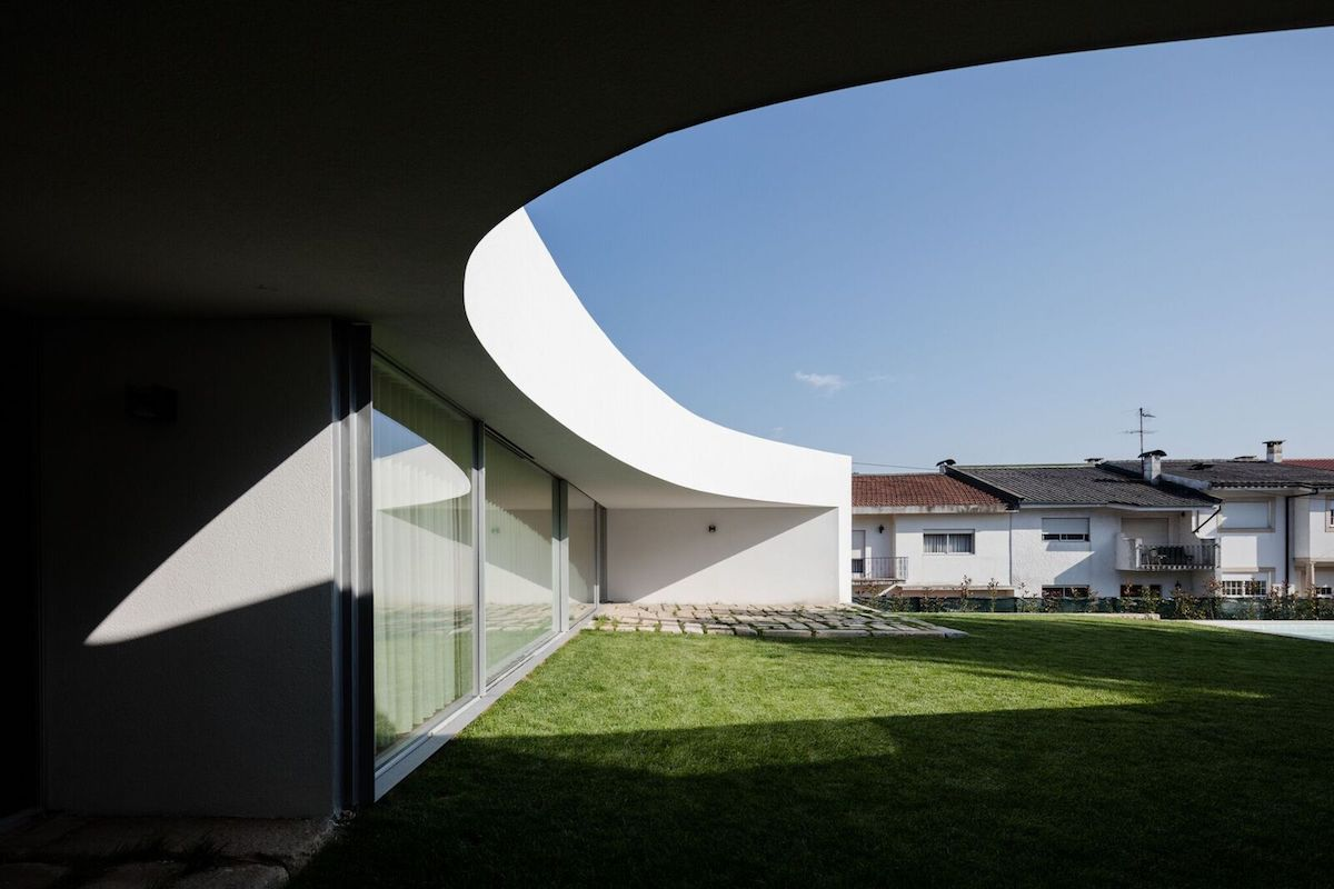 The way in which the facade arches and curves allows the house to stand out from the neighboring structures