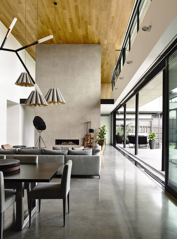 The fireplace wall doubles as a space divider and is in tone with the overall minimalism design of this volume