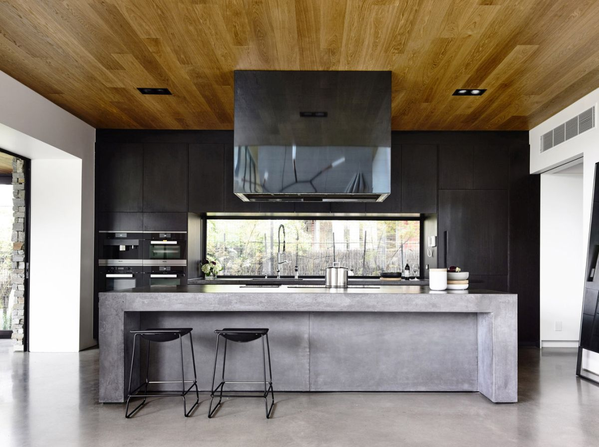 The kitchen has a large stone island which also serves as a bar and as a space divider