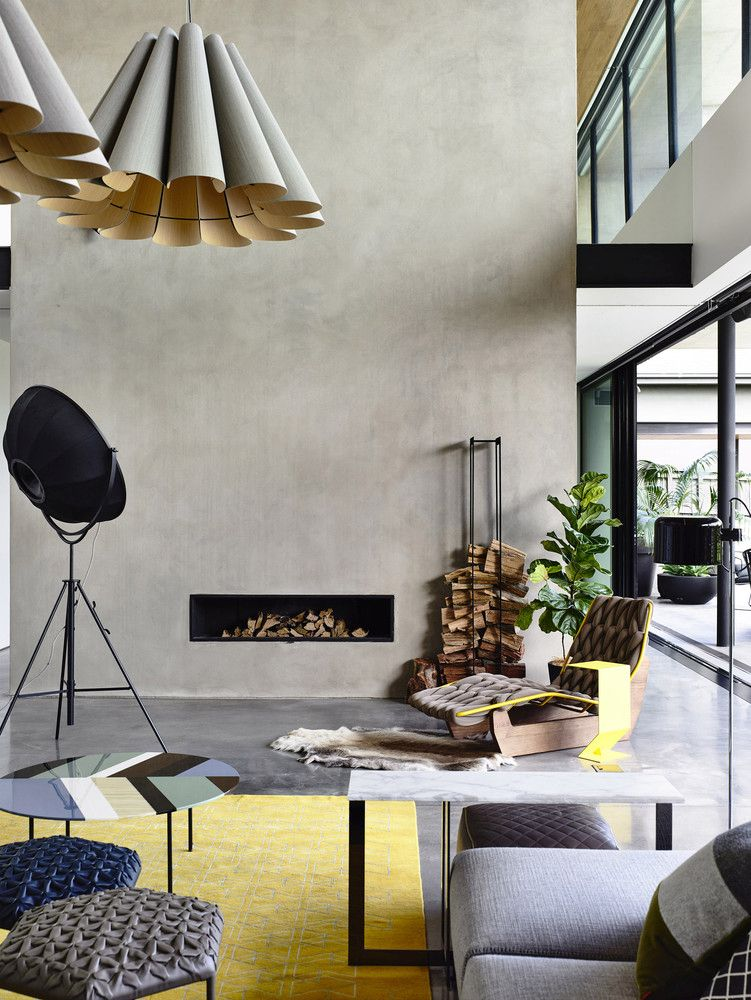 The double-height living area features polished concrete floors, a minimalist fireplace and oversized pendant lamps
