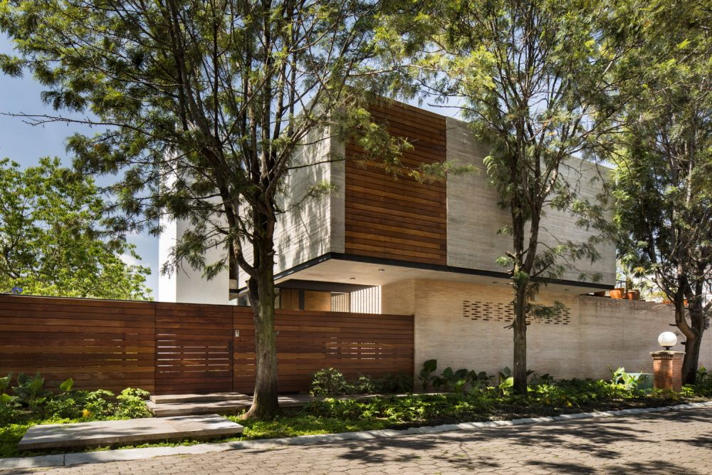 The wooden shutters and the matching privacy fence balance out the concrete volumes