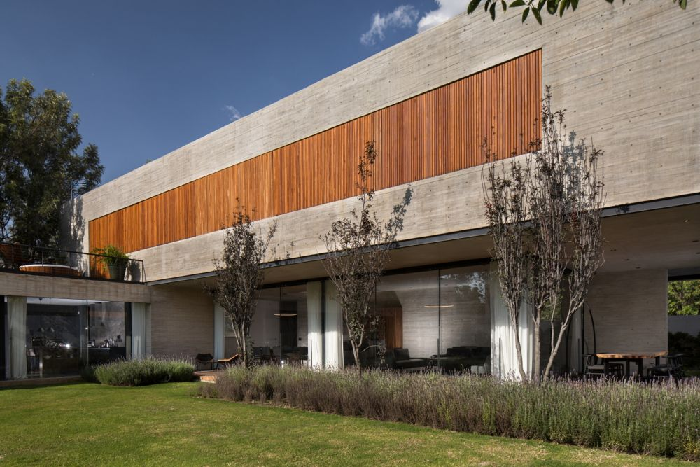 The closed wooden shutters sit flush with the outer concrete facade, giving the house a minimalist appearance