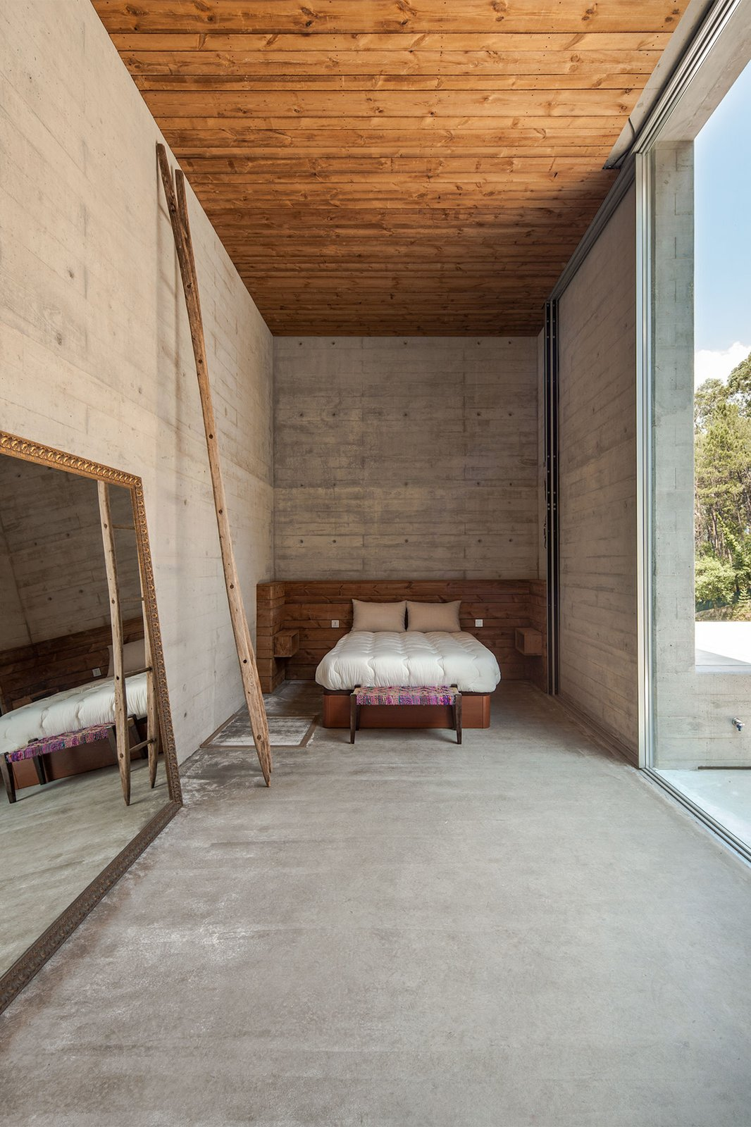 A wood-paneled ceiling and wooden furniture balances the decor of this bedroom, adding a warm touch
