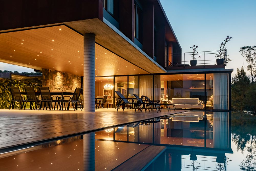The ground floor extends outside onto a large patio and a wooden deck which frames the swimming pool