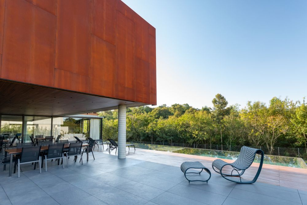 The large open patio overlooks the pool and serves as a transitional space between the indoor and the outdoor