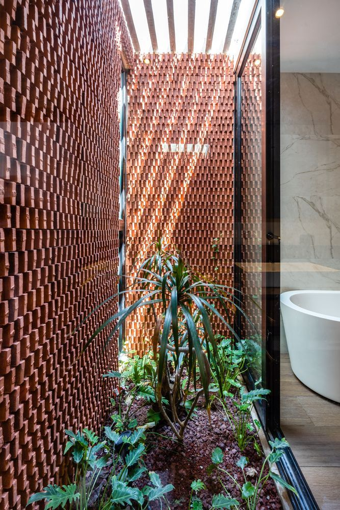 The bathroom has a beautiful little courtyard with perforated walls and sunlight coming in from above