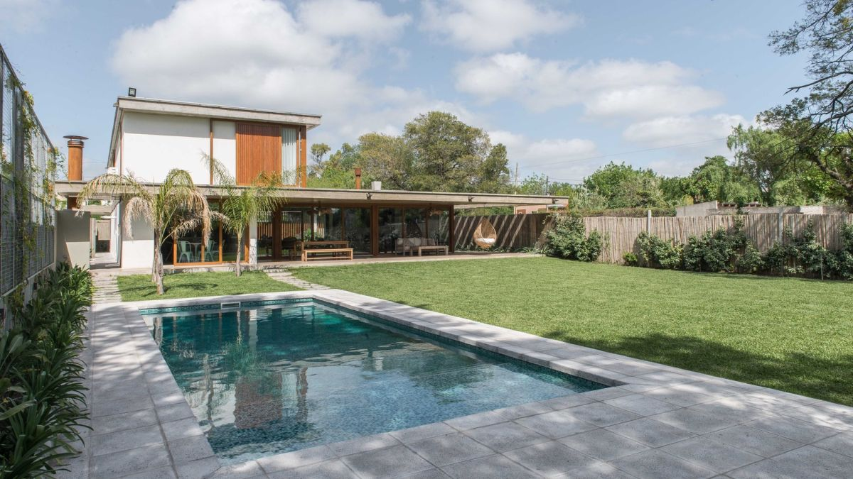 The backyard swimming pool is positioned along one of the side walls, leaving room for a manicured lawn