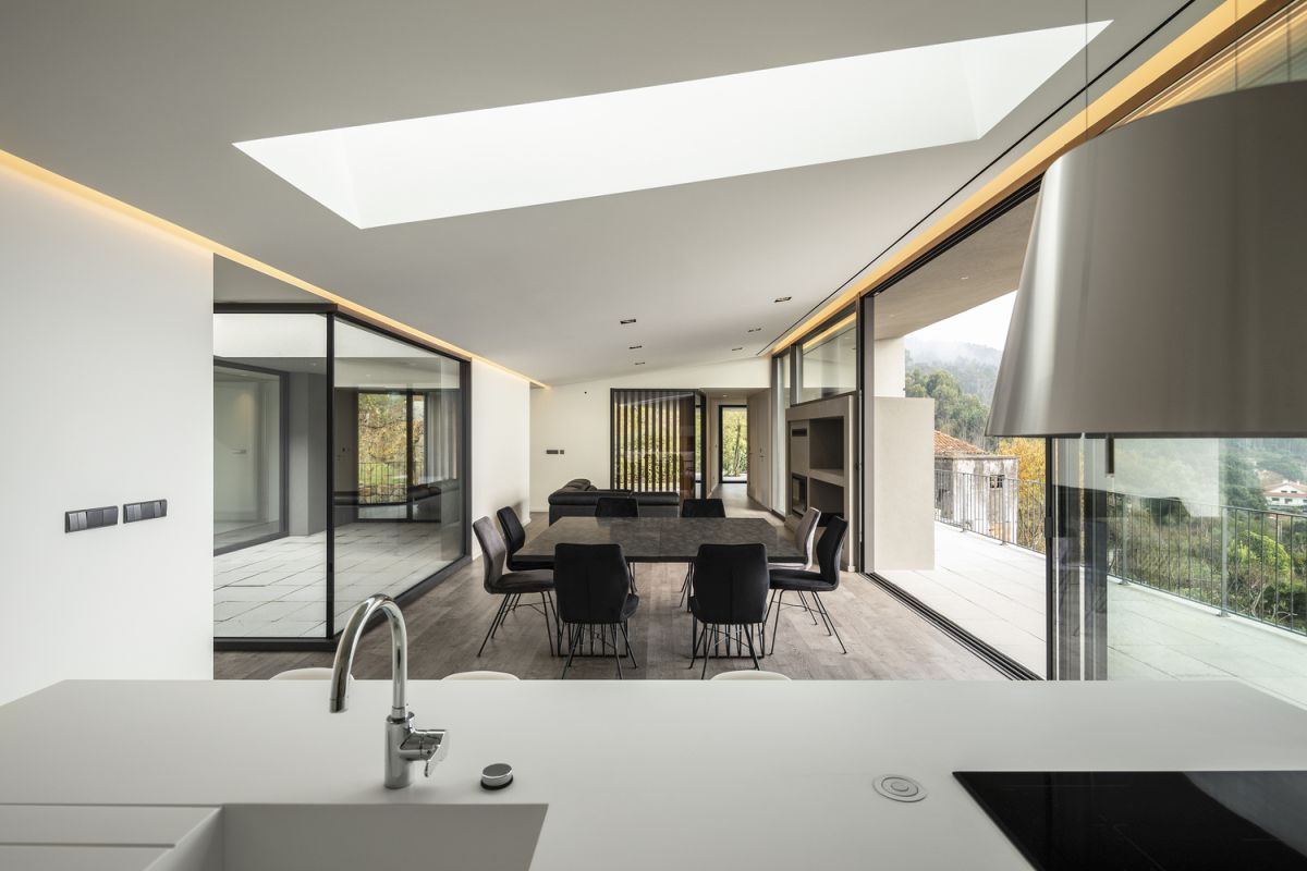 The kitchen, dining room and living area share an open plan with full-height panorama windows and skylight lighting