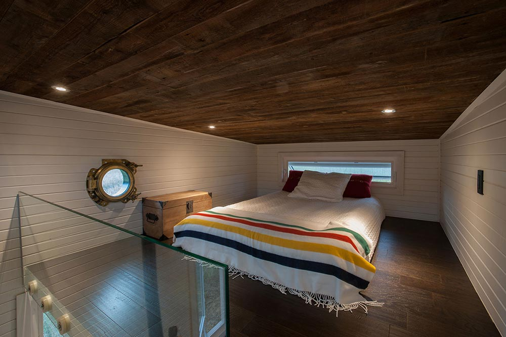 The loft bed has a glass railing and a thin window behind the bed