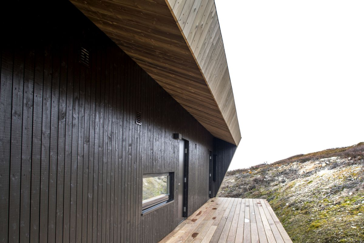 The body of the cabin is painted black which allows it to contrast with the roof and deck and to look modern and stylish