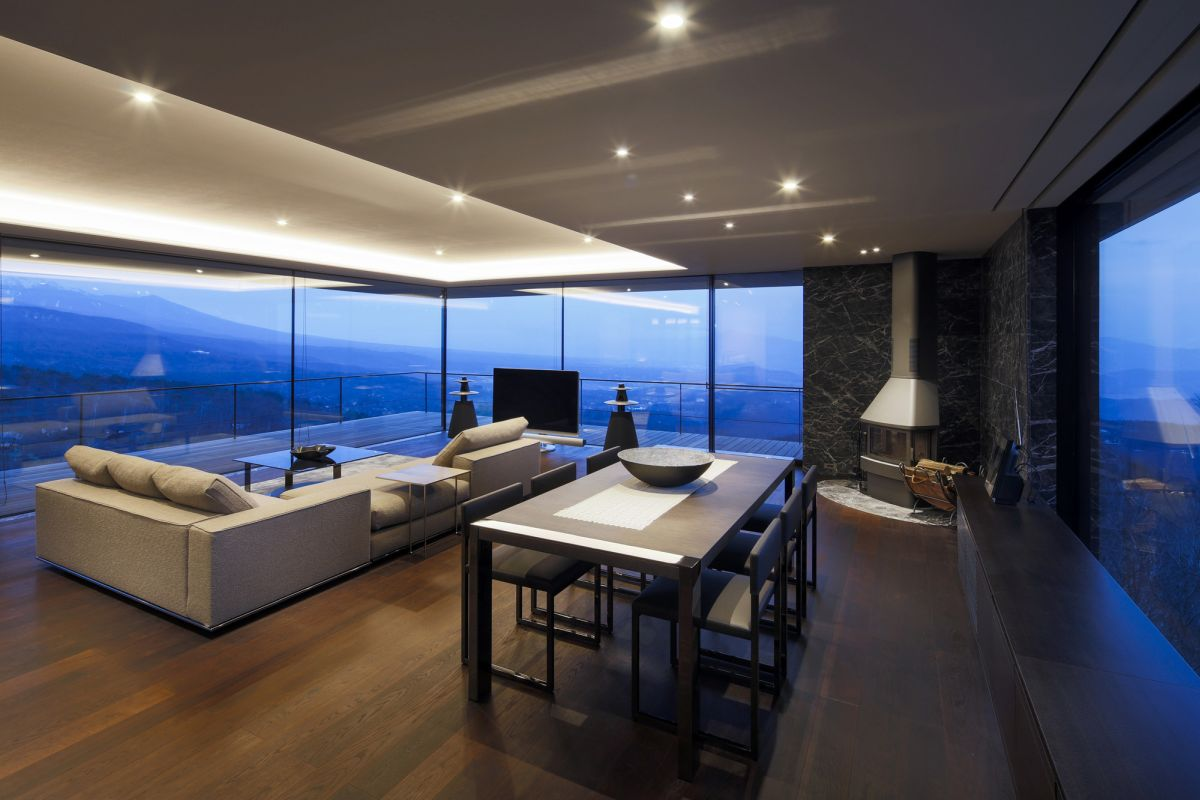 The living area is almost entirely wrapped in glass only. An exception is one corner of the space which accommodates a fireplace