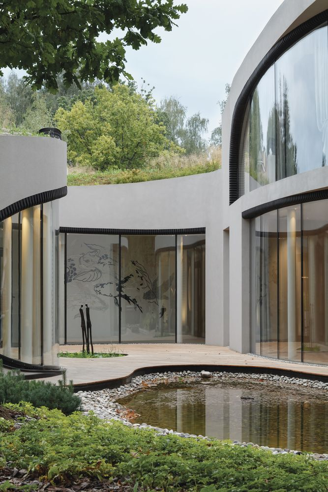 The large windows and openings curve and follow the organic outline of the building