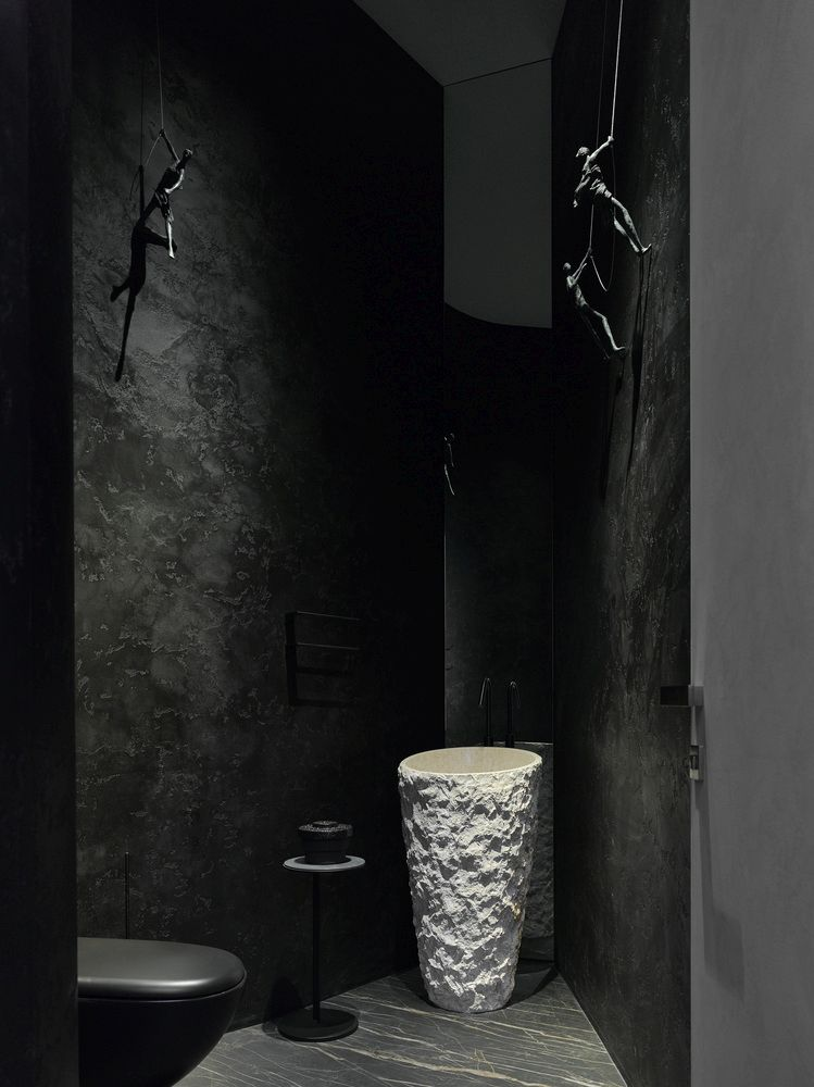 The black bathroom design contrasts with that of the rest of the house but in a pleasant way