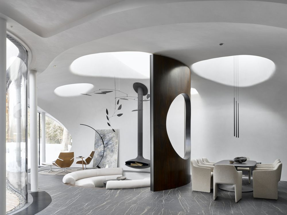The sunken living room has a ceiling-mounted fireplace and eye-catching light fixtures that resemble contemporary sculptures