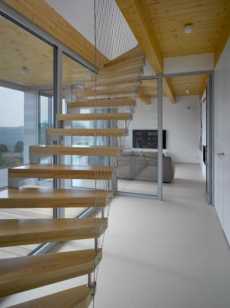 The two floors are connected via floating staircase with treads made of wood and suspended with thin metal cables
