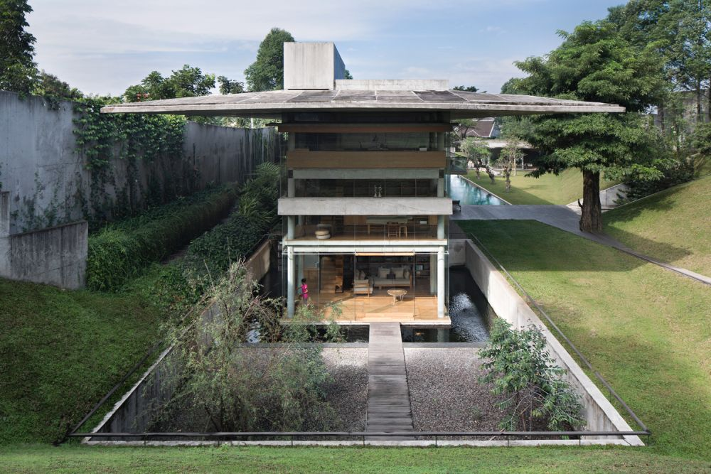 The house has an oversized roof with wide eaves that offer shade and protection from the rain