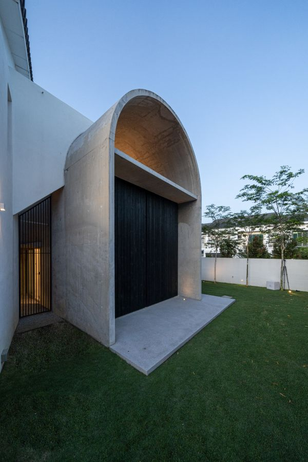 The arched roof extends out into the garden and forms a beautiful entrance