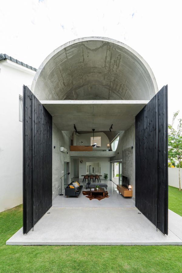 The arched section features oversized wooden doors which allow it to flow into the garden