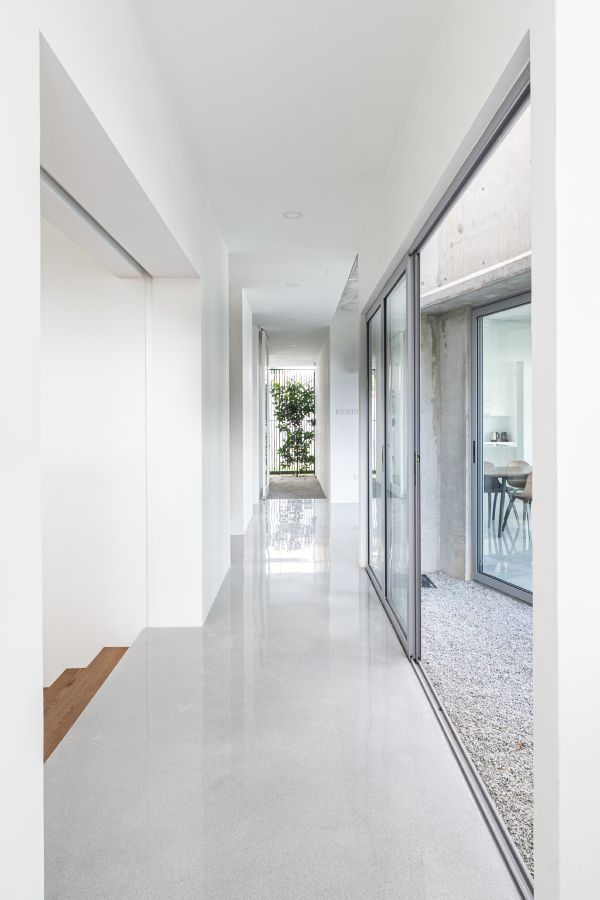 The unfinished concrete walls of the extension contrast with the original house design