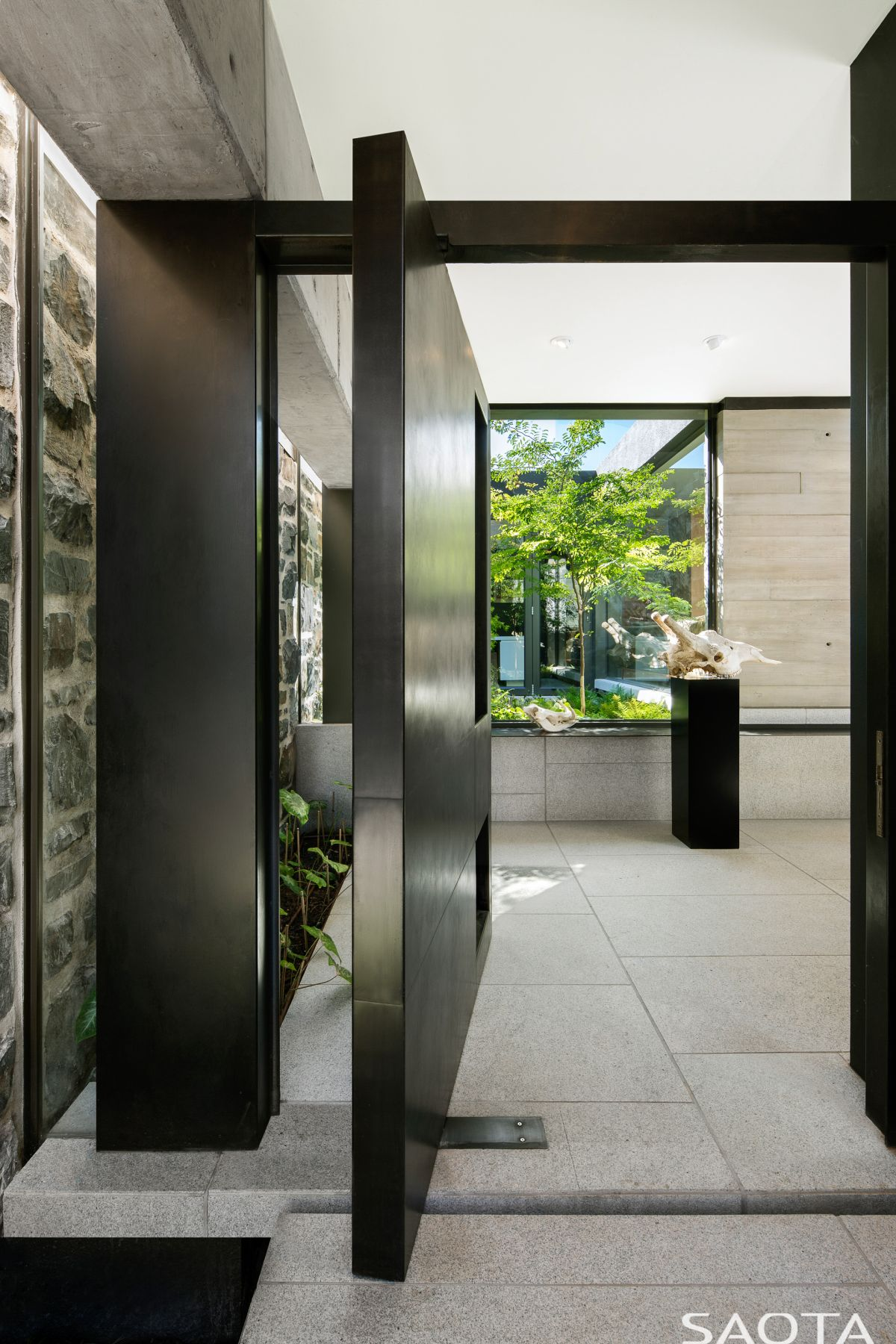 The front door is large and made of metal and it has a pivoting system