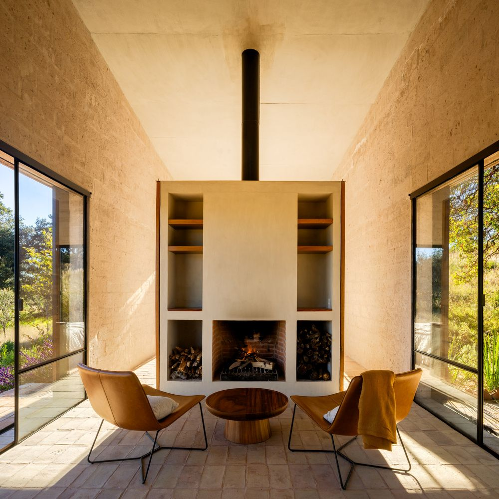 A cozy fireplace area framed by large windows on two sides serves as one of the central areas inside the house