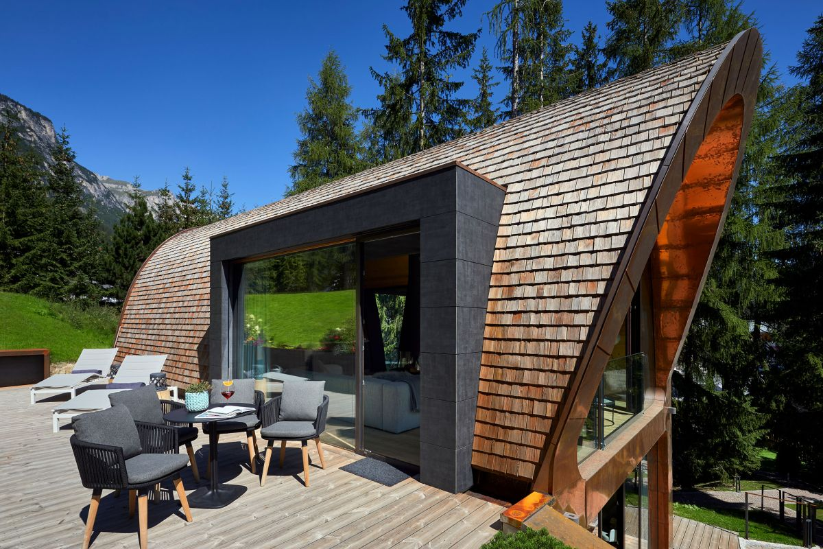 The curved facade is interrupted by a large opening on the side which connects the interior spaces to a wooden deck