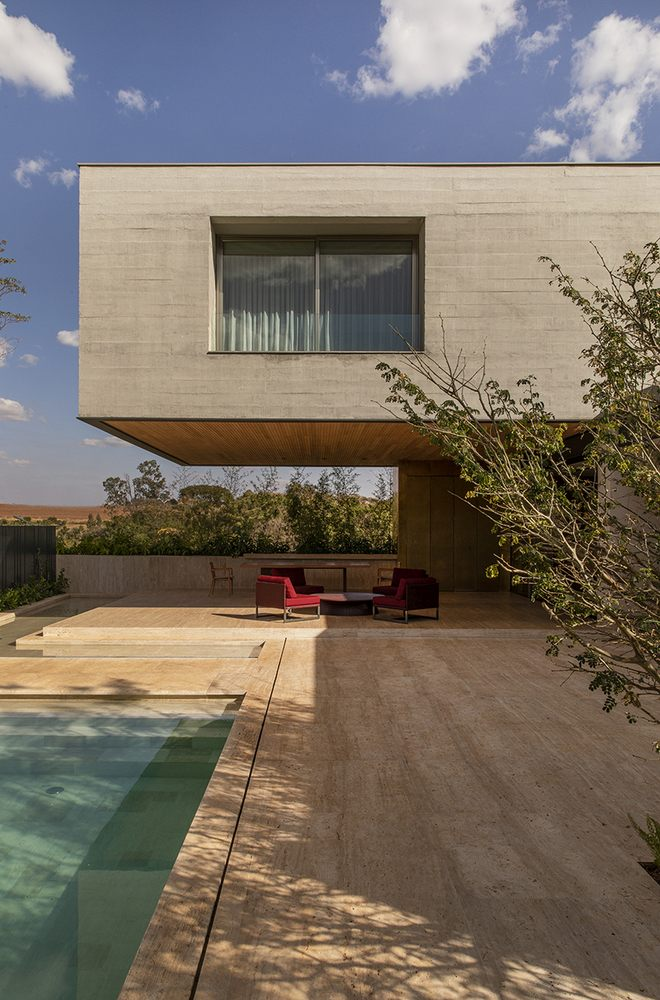 The upper floor extends over the side overhanging over the poolside deck