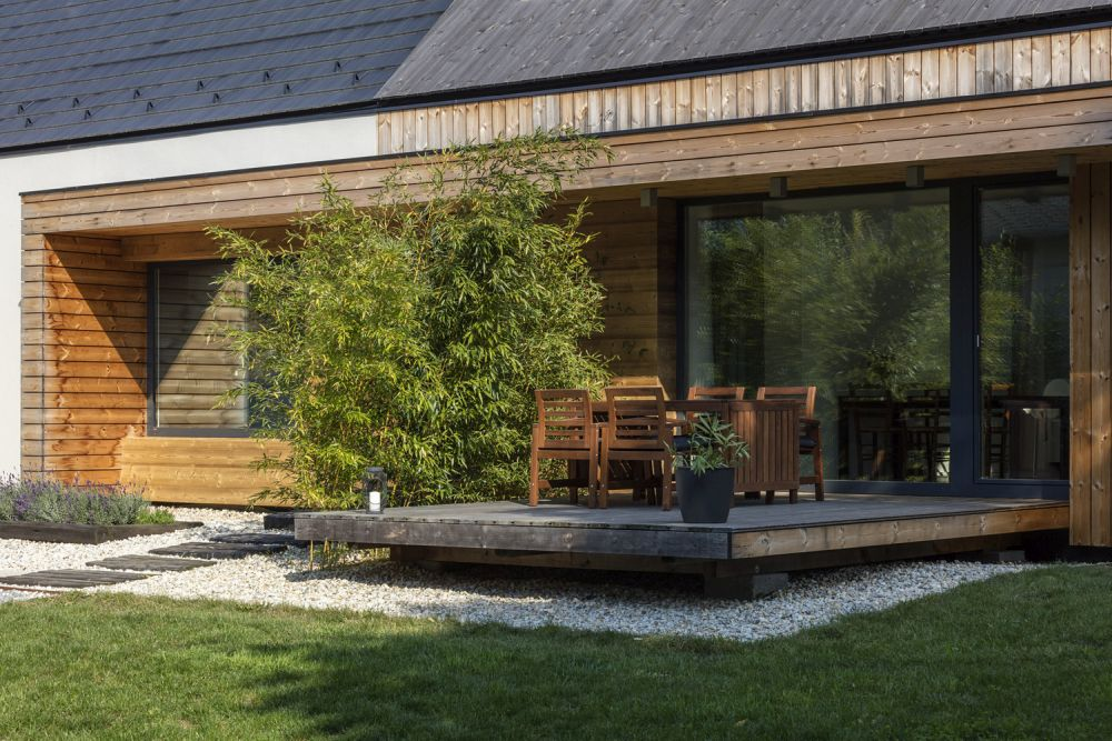 A small deck extends the living area into the backyard, sitting perpendicularly to the main floor plan