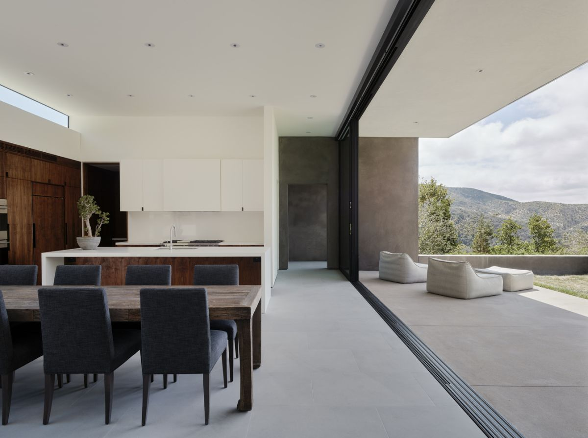 Large sliding glass doors ensure a seamless transition between the living area, the adjacent deck and the landscape that unfolds beyond it