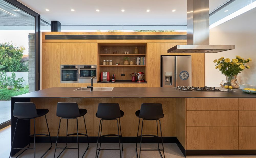The kitchen is open and features a large island with a very thin and slender top complemented by bar stools
