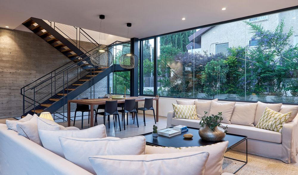 The wood and metal staircase which connects the floors is complemented by a matching dining table set