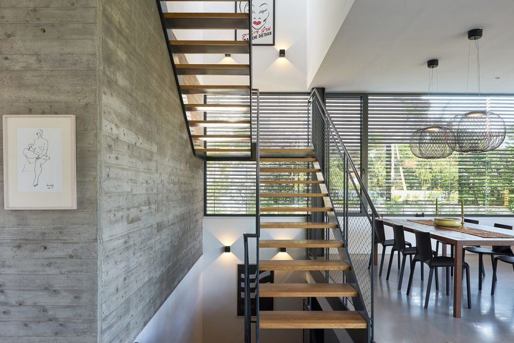 Full-height windows open up the living areas towards the garden allowing sunlight to enter the space