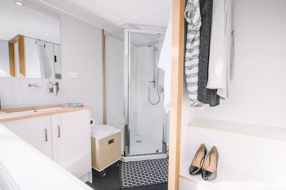 The bathroom is space0efficient and features a small shower in one of the corners