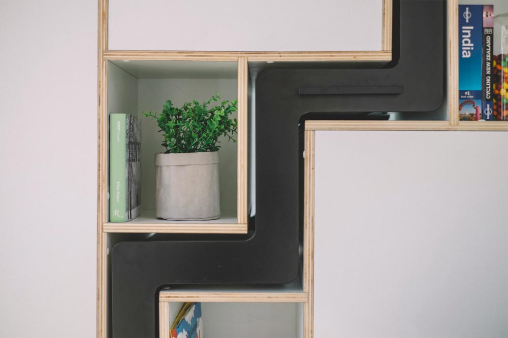 When the staircase is not needed is slides into the custom-built wall unit, becoming flush with the shelves