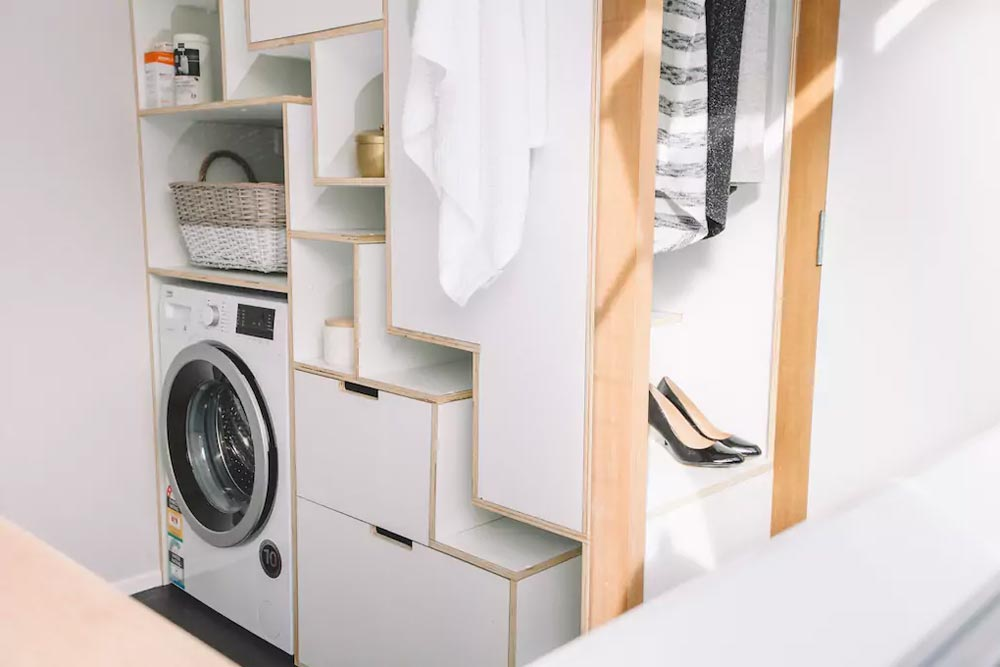 A compact laundry area features another custom storage unit with space for a washer/dryer