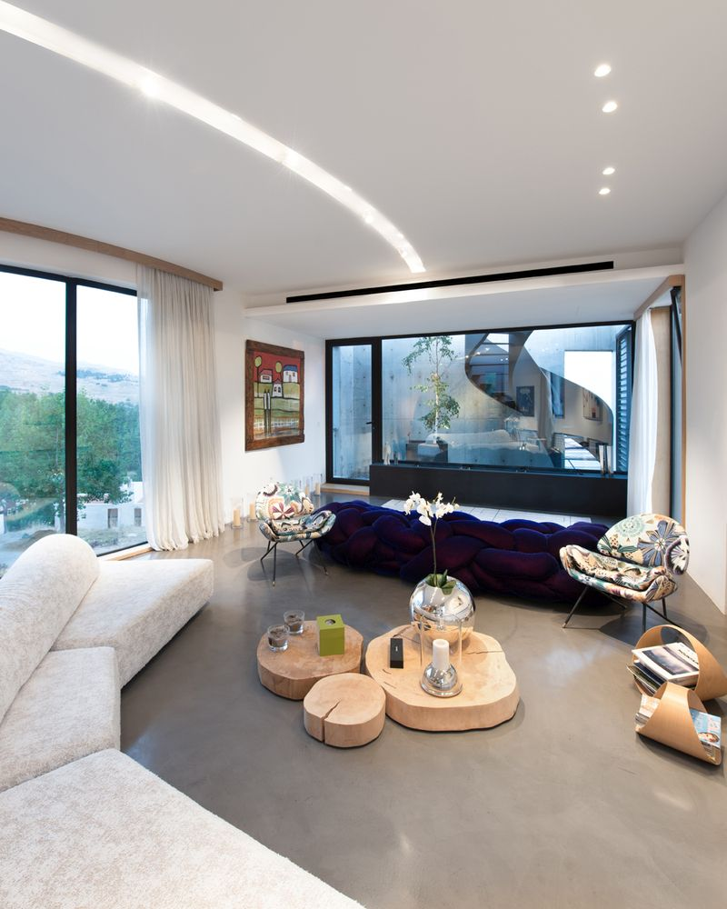 The interior spaces are organized on two floors, with the living spaces being situated on the upper level