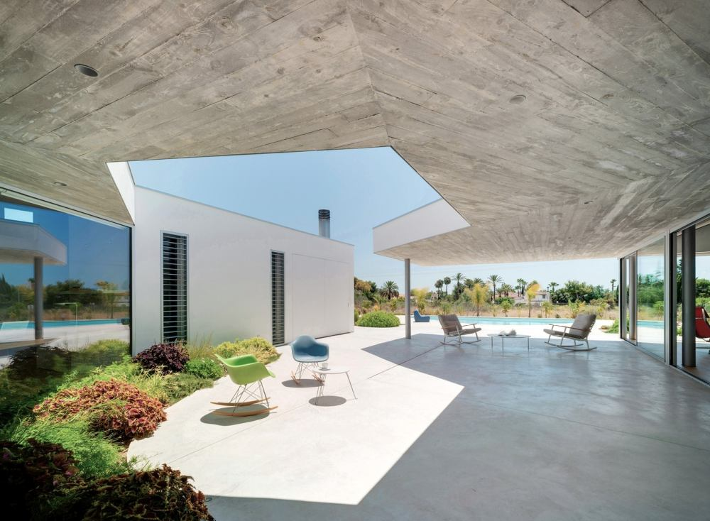 The U-shaped floor plan wraps around a courtyard with a large patio