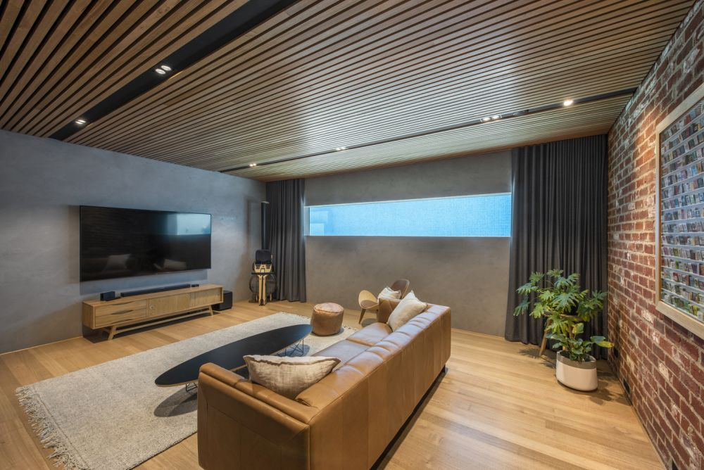 This cozy living area has a super narrow horizontal window and a stylish wooden ceiling